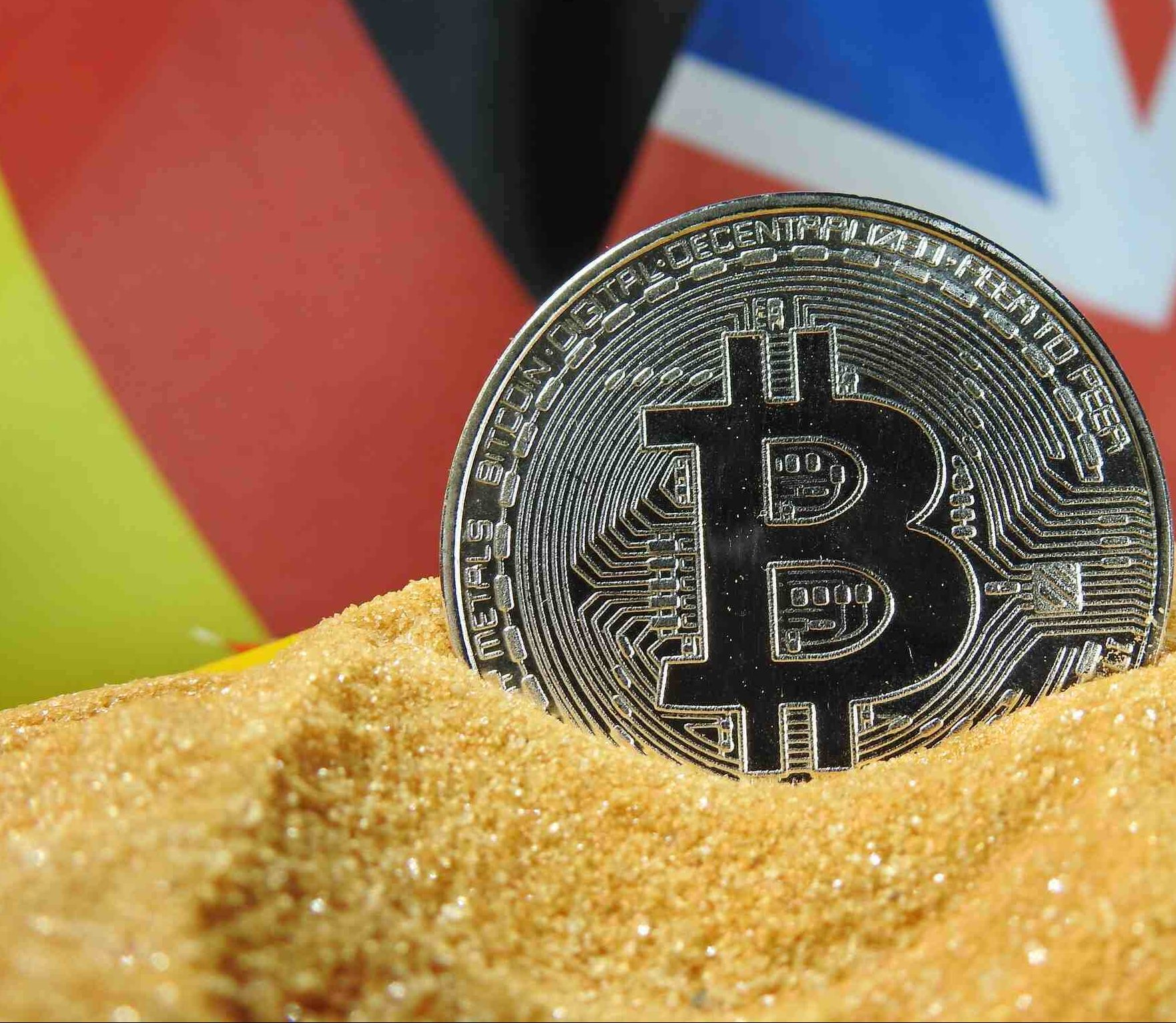bitcoin with uk and german flgas behind it